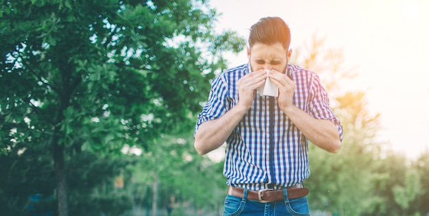 Foto van een jonge man met zakdoek. zieke man heeft loopneus.