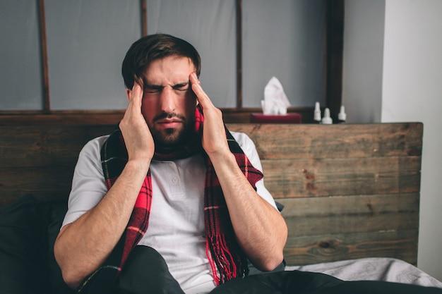 Foto van een jonge man met zakdoek. zieke man ligt in bed en heeft een loopneus. man maakt een remedie voor de verkoudheid. model man heeft een hoge temperatuur, hoofdpijn, migraine