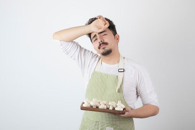 Foto van een jonge mannelijke kok die rauwe champignons vasthoudt en moe wordt