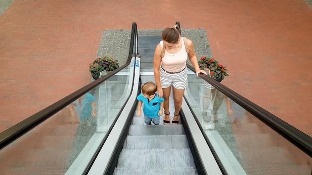 Foto van een jonge moeder die haar zoontje met de hand vasthoudt tijdens het rijden op de roltrap in het winkelcentrum
