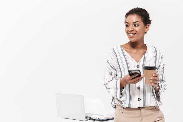 Foto van een jonge mooie afrikaanse vrouw die zich voordeed over een witte muur met behulp van een mobiele telefoon die koffie drinkt.