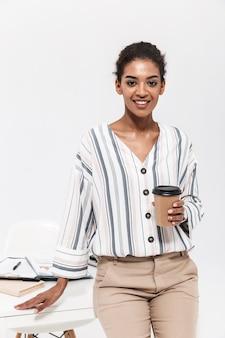 Foto van een jonge mooie afrikaanse vrouw poseren geïsoleerd over witte muur koffie drinken.
