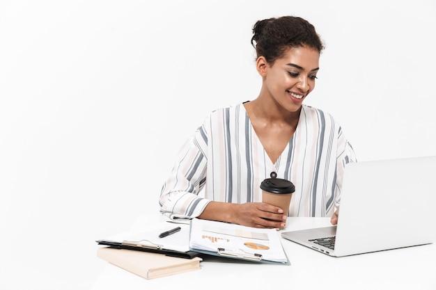 Foto van een jonge mooie afrikaanse vrouw poseren geïsoleerd over witte muur met behulp van laptopcomputer koffie drinken.