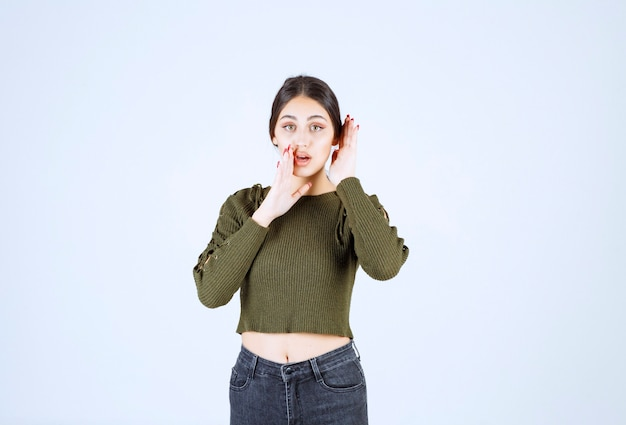 Foto van een jonge, mooie vrouw die iets fluistert terwijl ze naar de camera kijkt.