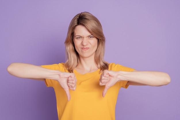 Foto van een jonge, overstuur serieuze aantrekkelijke meid die een duim omlaag laat zien, afkeuren, afkeuren, geïsoleerd op een paarse kleur achtergrond