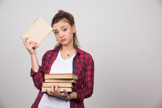 Foto van een jonge student die een stapel boeken vasthoudt.