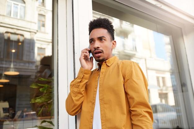 Foto van een jonge verbaasde man met een donkere huidskleur in een geel overhemd die over straat loopt, aan de telefoon spreekt, ongelooflijk nieuws hoort, met wijd open mond en ogen, ziet er versuft uit.