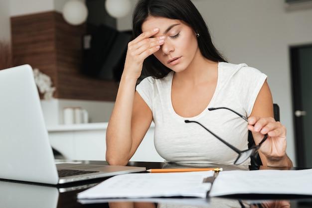 Foto van een jonge vermoeide vrouw die de financiën van het huis analyseert met een laptop terwijl ze last heeft van vermoeide ogen en een bril vasthoudt.
