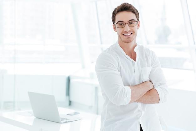 Foto van een jonge vrolijke man gekleed in een wit overhemd dat boven een wit raam staat. camera kijken.