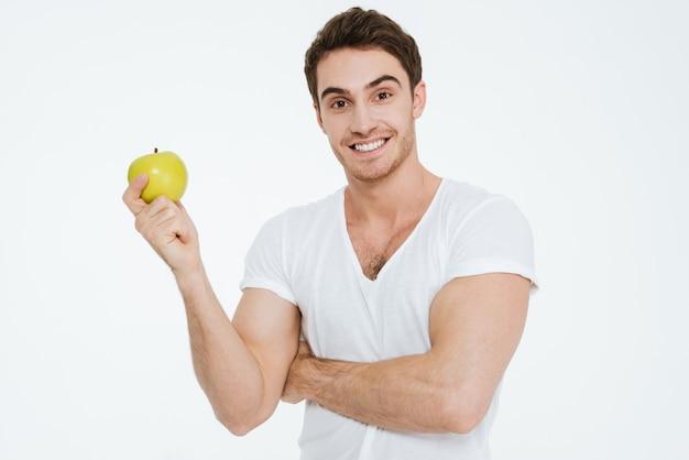 Foto van een jonge vrolijke man gekleed in een wit t-shirt dat over een witte achtergrond staat en een alarm toont aan de camera met appel.