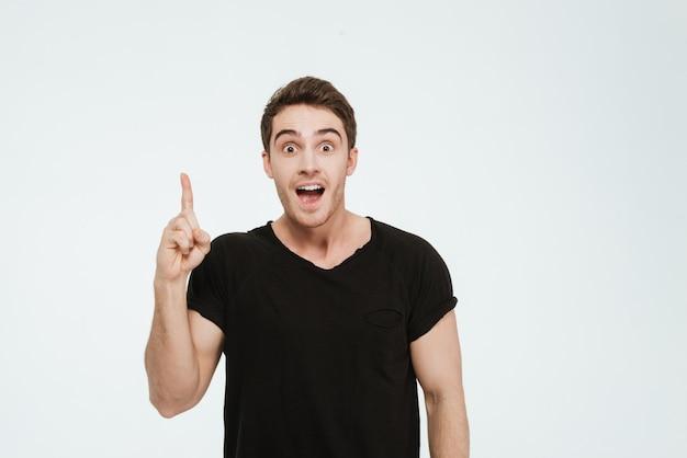 Foto van een jonge vrolijke man gekleed in een zwart t-shirt dat over een witte achtergrond staat en naar de camera kijkt en een idee heeft.