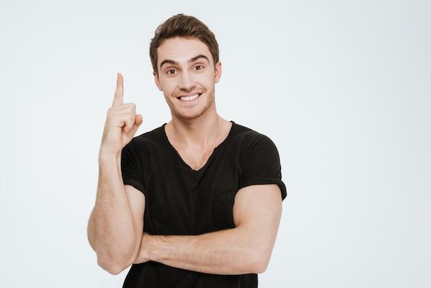 Foto van een jonge vrolijke man gekleed in een zwart t-shirt dat over een witte achtergrond staat en naar de camera kijkt terwijl hij wijst.