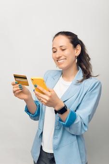 Foto van een jonge vrolijke vrouw in casual die een overschrijving maakt met creditcard en smartphone