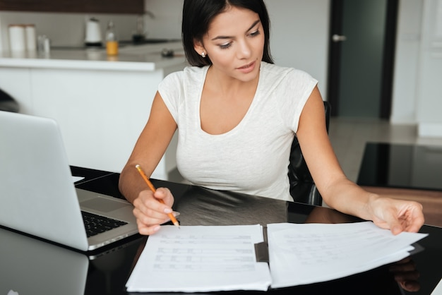 Foto van een jonge vrouw die de financiën van het huis analyseert met een laptop terwijl ze naar documenten kijkt.