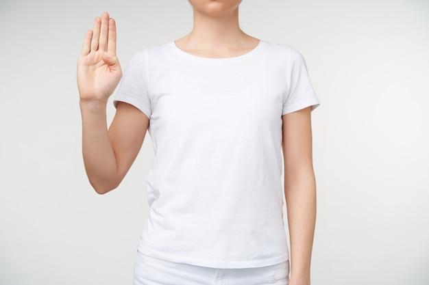 Foto van een jonge vrouw die doof alfabet leert en letter b vormt met opgeheven hand, wordt geïsoleerd op witte achtergrond in wit basis t-shirt