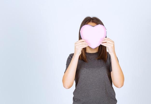 Foto van een jonge vrouw die haar gezicht bedekt met een hartvormige geschenkdoos.