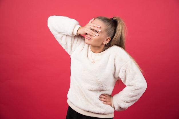 Foto van een jonge vrouw die haar ogen behandelt met haar handen