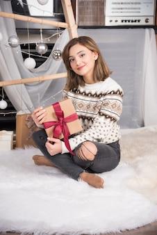 Foto van een jonge vrouw die op het tapijt zit en een kerstcadeau vasthoudt