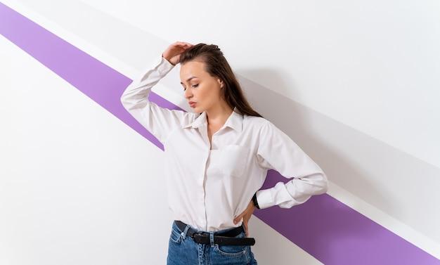 Foto van een jonge vrouw gekleed in een wit overhemd. staan nog steeds geïsoleerd over witte muur met violette streep.