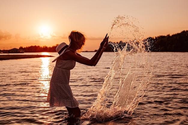Foto van een jonge vrouw in het water zijaanzicht een mooie gelukkig lachende blonde in een zomerjurk en...
