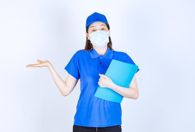 Foto van een jonge vrouw in uniform die een medisch masker draagt en een map vasthoudt.
