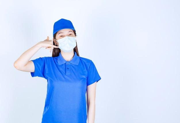 Foto van een jonge vrouw in uniform die een medisch masker draagt en een telefoongebaar maakt.