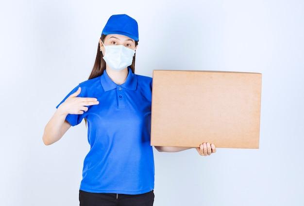 Foto van een jonge vrouw in uniform en medisch masker met papieren doos.
