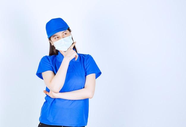 Foto van een jonge vrouw in uniform met een medisch masker en poseren.