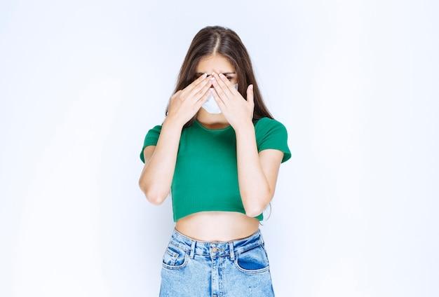 Foto van een jonge vrouw met een beschermend medisch masker dat ogen bedekt met handen.
