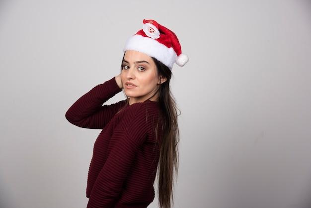 Foto van een jonge vrouw met een kerstmuts die naar de camera kijkt.