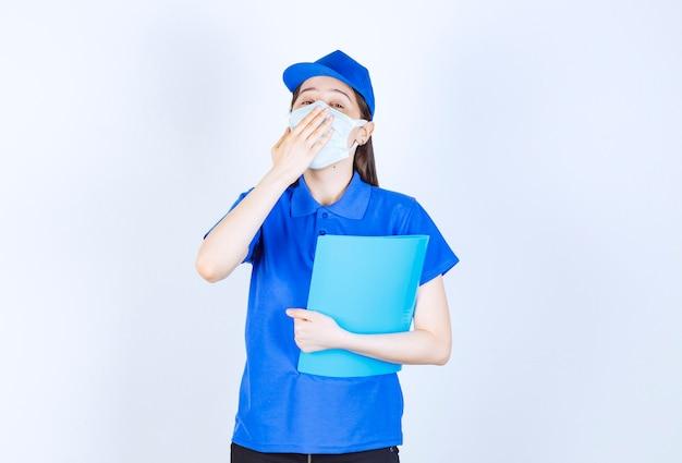 Foto van een jonge vrouw met een medisch masker die een map vasthoudt en geeuwen.