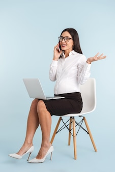 Foto van een jonge zwangere bedrijfsvrouw die met lap top computer wordt geïsoleerd die door mobiele telefoon spreekt.