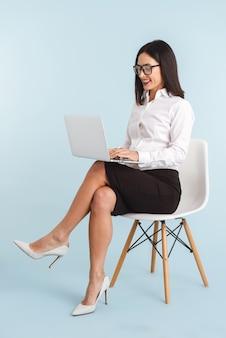 Foto van een jonge zwangere bedrijfsvrouw die met lap top computer wordt geïsoleerd.