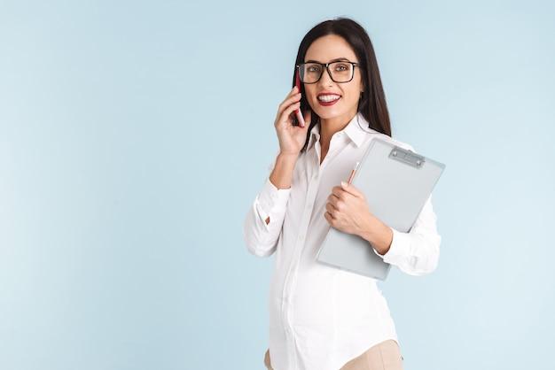 Foto van een jonge zwangere bedrijfsvrouw geïsoleerd holdingsklembord die door mobiele telefoon spreekt.
