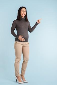 Foto van een jonge zwangere geïsoleerde vrouw wijzend naar copyspace.