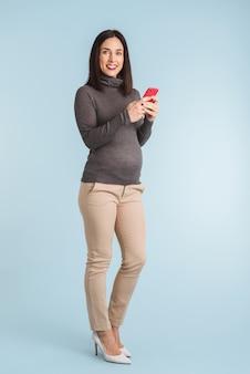 Foto van een jonge zwangere vrouw die met behulp van mobiele telefoon wordt geïsoleerd.