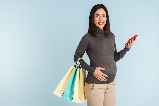 Foto van een jonge zwangere vrouw geïsoleerd met behulp van mobiele telefoon met boodschappentassen.