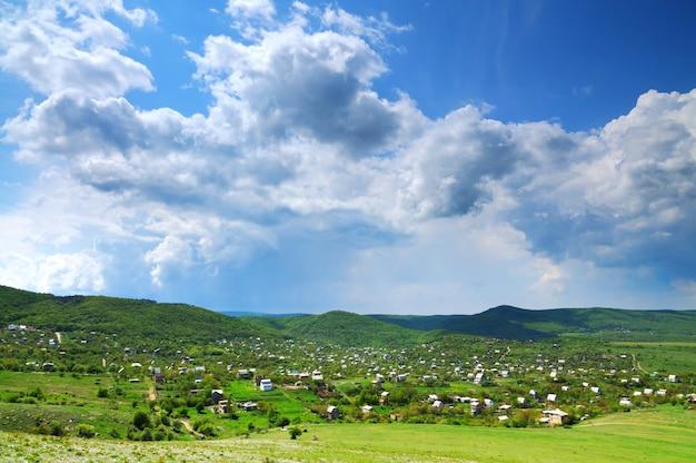 Foto van een klein dorp gelegen tussen de bergen.
