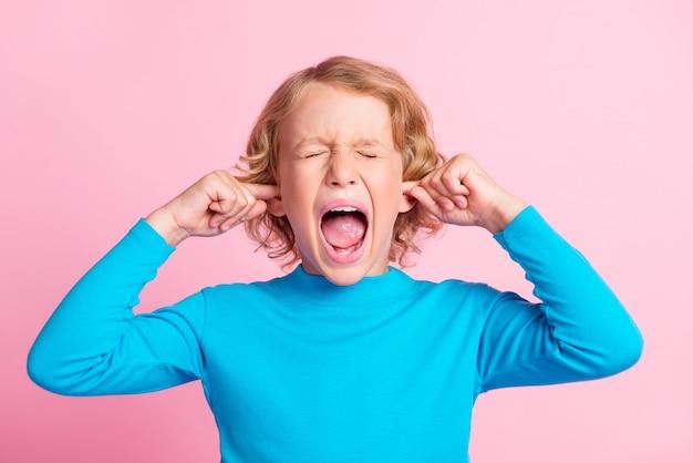 Foto van een klein gefrustreerd kind schreeuwt open mond sluit ogen vingers bedek oren draag blauwe coltrui geïsoleerde pastelroze kleur achtergrond