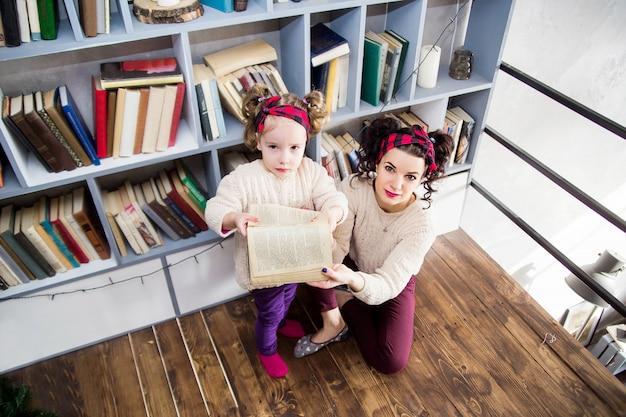 Foto van een klein meisje en haar moeder zijn van streek vanwege een gescheurd boek