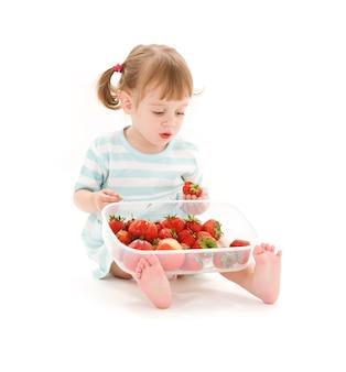 Foto van een klein meisje met aardbei over wit