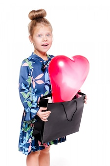 Foto van een klein modieus meisje in een blauwe bloemenjurk houdt een grote tas vast met een hartvormige ballon erin