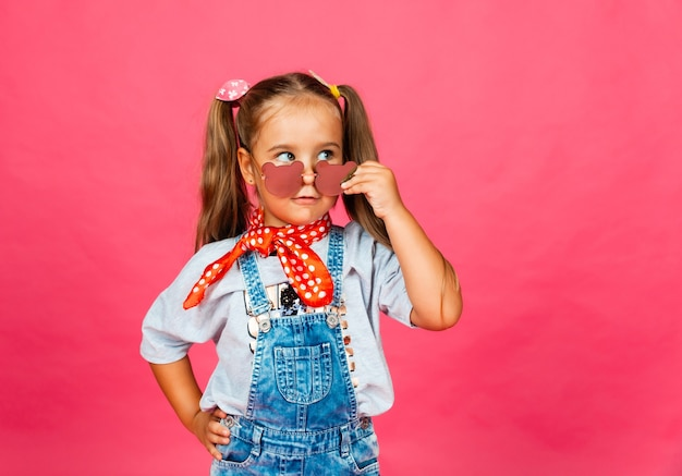 Foto van een klein schattig mooi meisje dat geïsoleerd op een roze achtergrond staat, een zonnebril draagt en naar de camera kijkt.