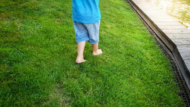 Foto van een kleine peuterjongen op blote voeten die in het park op vers groen gras rent
