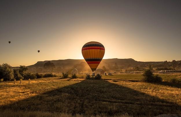 Foto van een kleurrijke hete luchtballon in een veld omringd door groen en bergen tijdens zonsondergang
