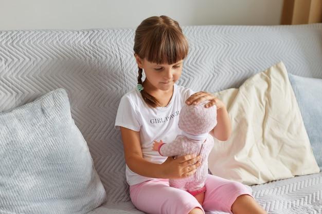 Foto van een kleutermeisje dat op de bank in de kamer thuis zit te spelen met een babypop als moeder, een kind met een wit t-shirt en een roze korte broek, jeugd.