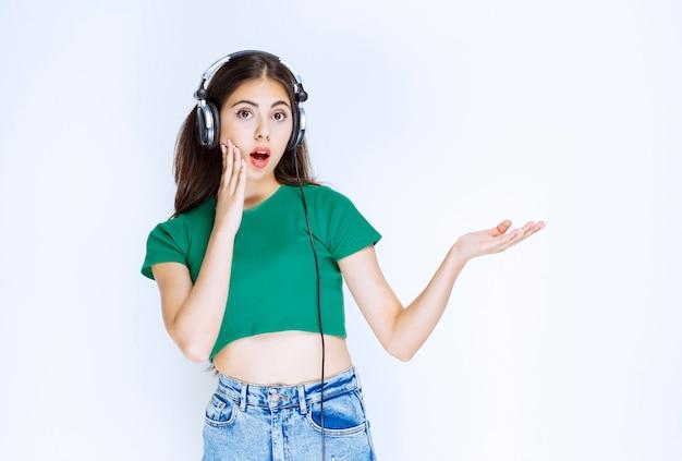Foto van een knap meisjesmodel dat met een koptelefoon staat en tegen de witte muur poseert.