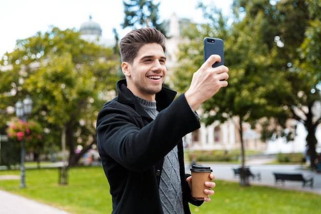 Foto van een knappe 30-jarige man met een jas die een selfie-foto maakt op een smartphone en afhaalkoffie drinkt terwijl hij door het stadspark loopt