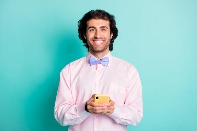 Foto van een knappe, brede kerel die een telefoon draagt, een overhemdsstropdas geïsoleerd op een turquoise gekleurde achtergrond