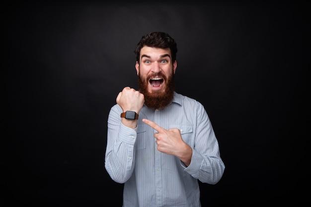Foto van een knappe gefrustreerde man met baard, vertraging en wijzend op horloge, met geschokt gezicht, permanent over donkere geïsoleerde achtergrond
